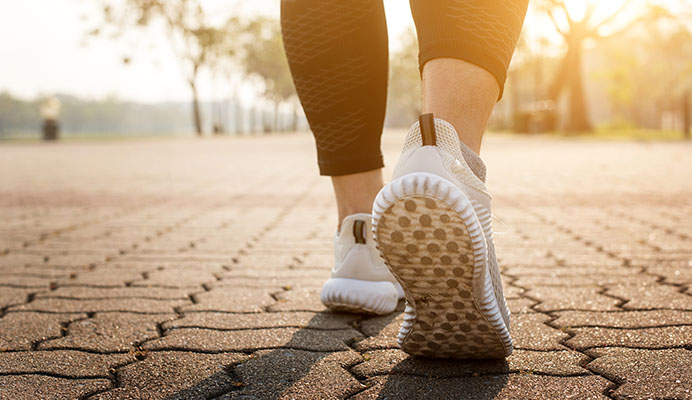 view of sneakers of woman walking to maintain wellness
